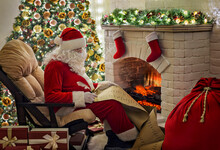 Old Kind Bearded Santa Claus Sitting At Armchair In His Cozy Home Room Near Christmas Tree, Fireplace, Xmas Stocking And Big Gifts Sack And Writing On Kids List Preparing For Holidays