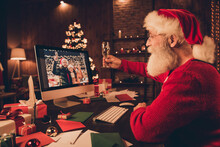 Profile Side Photo Of Aged Santa Claus Happy Positive Smile Speak Video Call Computer Cheers Drink Champagne Celebration Indoors