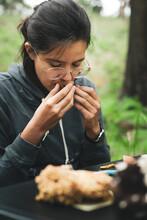 Female Sniffing Mushroom In Nature