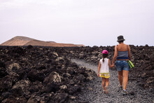 Unrecognizable Mother With Daughter Walking On Path Between Lava