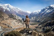 Tourist Admiring River Flowing Through Mountainous Landscape
