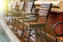 A Number Of Chairs And Tables Made Of Wood Are Covered With Drops Of Water.