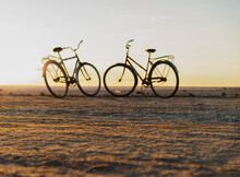 Silhouettes Of Two Bicycles Against The Sunset, Romance On A Summer Day. High Quality Photo
