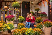 Portrait Of Two Happy Little Girls In Autumn In The Yard Near The House And Many Flowers