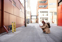 Man With Smart Phone Photographing Meter In Urban Alley