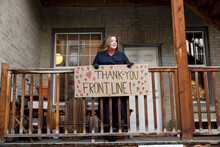 Smiling Woman Thanking Frontline Workers With Sign Outside Apartment