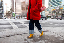 Stylish Woman In Red Coat And Yellow Boots Walking In City