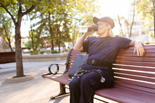 EMS Worker Drinking Water On Park Bench