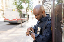 Security Guard Looking At Watch Beside Covered Bus Stop