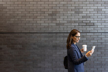 Businesswoman With Coffee Using Smart Phone At Brick Wall
