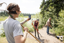 Man Taking Photo Of Friends Working In Forest