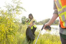 Conservation Volunteers Litter Picking Next To Lake