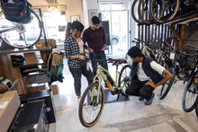 Owner Assisting Customers With Bicycle In Sports Store