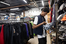 Young Owner Checking Cycling Helmet In Sports Store