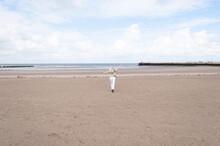 Tiny Woman Runs Open Arms Along The Beach To The Sea