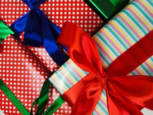 Lots Of Gifts Wrapped In Colorful Paper, Decorated With Red, Blue And Green Bows.