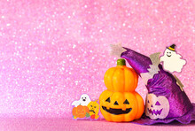 Concept Photography Depicting An Halloween Jack O Lantern Pumpkin Head And A Purple Witches Hat With Funny Ghost Smiling And Cardboard Cutout Bats Against A Glittering Pink Background.