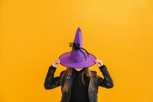 White Girl Wearing Witch Costume Hiding Into Hat While Posing At Camera