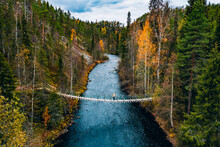 Aerial View Of Fall Forest And Blue River With Bridge In Finland.