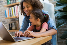 Mixed Race Girl Using Laptop For Learning With Mother