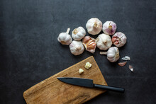 Garlic And Garlic Cloves And Sliced Garlic On Dark Grey Background.