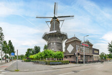 Old Windmill And Building Facade Against Urban Road