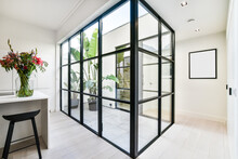 Glass Wall Against Blooming Flowers On Table In Modern House