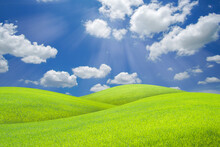 Landscape Of Green Grass Field On A Hill With Beautiful Blue Sky With Clouds. Ecology And Natural Background Concept.