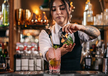 Young Female Mixologist Spraying Cocktail