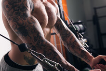 Powerful Sportsman Training On Cable Crossover Machine In Light Gym