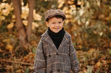 A Happy Child Boy In An Autumn Coat Walks In An Autumn Yellow Park.