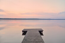 Forest Lake At Sunset. Wooden Pier. Soft Sunlight, Glowing Clouds, Symmetry Reflections In A Crystal Clear Water. Idyllic Landscape. Panoramic View. Nature, Ecology, Ecotourism. Peace And Joy Concepts