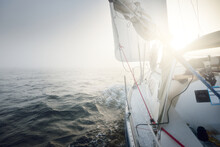 White Yacht Sailing In The Baltic Sea. Thick Fog. Sunrise. Sweden. Close-up View From The Deck To The Bow And Sails. Morning Sun, Glowing Clouds. Sport, Recreation, Leisure Activity, Cruise, Regatta