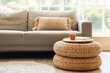 Leinwandbild Motiv Rattan poufs with cup of coffee and magazine in living room