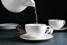 Pouring Of Tasty Hojicha Green Tea Into Cup On Black Background