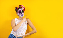 Mexican Catrina, Portrait Of Young Latin Woman Pointing Aside On Yellow Copy Space, Halloween Party In Mexico