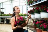 Friendly female gardener demonstrating garden flowers in flowerpots at garden store