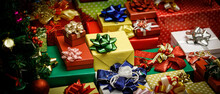 Close Up Shot Of A Lot Of Merry Christmas Eve Wrapped Present Gift Boxes Stack With Colorful Ribbons And Bows With Decoration Xmas Pine Tree With Glossy Sphere Balls Bells Socks Ice Flakes Nearby