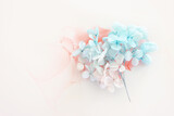 Creative image of pastel blue and pink Hydrangea flowers on artistic ink background. Top view with copy space