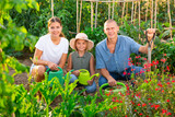 Portrait of daughter and parents with watering cans in the summer garden