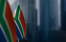 Small Flags Of South Africa On A Blurry Background Of The City