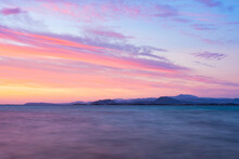 Stunning Seascape With A Romantic And Relaxing Sunrise Reflected On A Calm Water Flowing In The Foreground. Golfo Aranci, Sardinia, Italy.