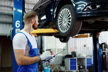 Young Technician Mechanic Man 20s Wears Denim Overalls Use Hold Clipboard Papers Document Writing Estimate Stand Near Car Lift Check Technical Condition Work In Vehicle Repair Shop Workshop Indoors.