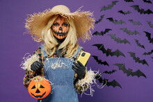 Young Woman With Halloween Makeup Mask In Straw Hat Scarecrow Costume Hold Jack-o'-lantern Pumpkin Mobile Cell Phone Isolated On Plain Dark Purple Background Studio Celebration Holiday Party Concept.