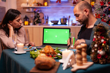 Happy Family Looking At Green Screen Mock Up Chroma Key Tablet With Isolated Display Standing On Xmas Decorated Table. Couple Celebrating Christmas Holiday Enjoying Winter Season Together