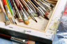 Various Paint Brushes On Painted Canvas