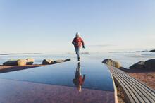 A Boy Runs On A Mirror Surface On A Sunny Day