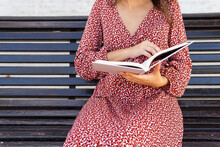 Anonymous Female Sitting With Opened Book In Bench In Daytime