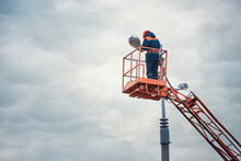 Street Light Repair Works, Worker Repair Street Lamp At Height, Led Lights Replacement. Man In Lift Bucket Wearing Personal Protective Equipment Fix Light Pole Lamp.