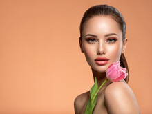 Beautiful White Girl With Flower. Stunning Girl With  Pink Tulip. Closeup Face Of Young Woman With A Healthy Clean Skin.